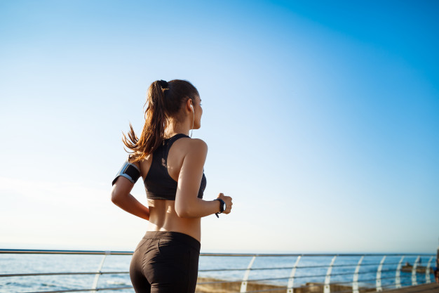 picture-young-attractive-fitness-woman-jogging-with-sea-wall_176420-16757