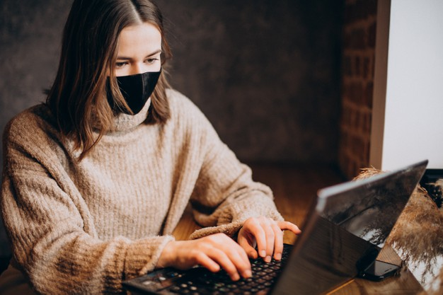 young-woman-working-laptop-cafe-wearing-mask_1303-26331